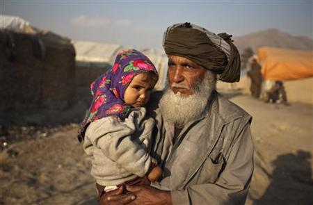 A displaced Afghan man from Helmand province carries his grandchild in Kabul, January 24, 2010. REUTERS/Ahmad Masood