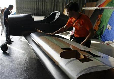 A man places a prototype cork wing on top of the currently-used plastic wing in DynAero's light plane to verify measurements, in a hangar at the Evora airfield September 20, 2009. REUTERS/Nacho Doce/Files