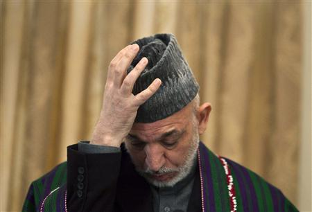 Afghan President Hamid Karzai adjusts his hat during a news conference in Kabul January 31, 2010. REUTERS/Ahmad Masood