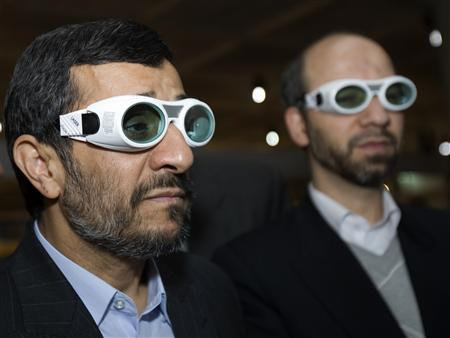 Iran's President Mahmoud Ahmadinejad (L) and Industries Minister Ali Akbar Mehrabian wear protective glasses while visiting an exhibition of Iran laser science and technology in Tehran February 7, 2010. REUTERS/Raheb Homavandi