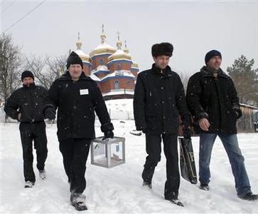Members of a local election commission walk in front of the church as they bring a ballot box to a voter's house during the presidential election in the village of Kozova, about 140 km (87 miles) south from the city of Lviv, February 7, 2010. REUTERS/Vitaliy Hrabar