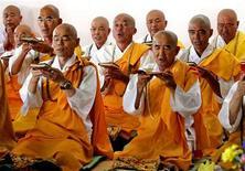 <p>Японские монахи-буддисты молятся в храме в Нагасаки 8 августа 2005 года. Во имя буддизма этот японский монах готов на все - он не просто рассказывает сутры, а еще и накладывает их на рэп-музыку. REUTERS/Yuriko Nakao</p>