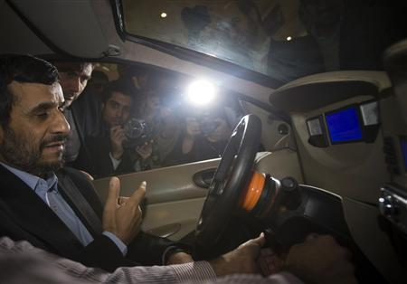 An Iranian student of the Shahid Rajai University explains as Iranian President Mahmoud Ahmadinejad sits in an electric vehicle during his visit to the 2nd National Festival of Innovation and Prosperity in Tehran February 8, 2010. REUTERS/Morteza Nikoubazl