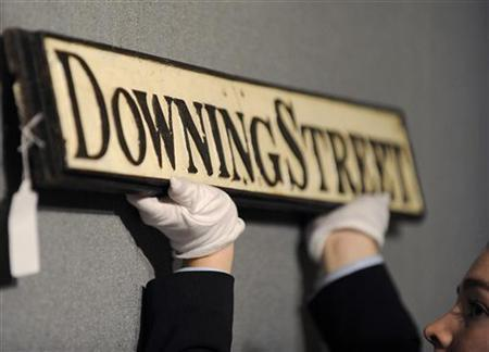 Furniture specialist Zelina Burt poses for photographers with an old street sign for Downing Street, at Bonhams auctioneers in central London January 14, 2010. REUTERS/Toby Melville