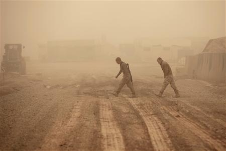 U.S. Marines walk during a dust storm in a U.S Marines camp near the town of Marjah in Nad Ali district of Helmand province, February 8, 2010. REUTERS/Goran Tomasevic