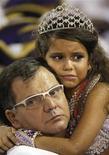 <p>La reina de tambores de la escuela de samba Viradouro Julia Lira, de siete años, llora en brazos de su padre, el presidente de Viradouro Marco Lira en la primera noche de desfile del Carnaval de Río de Janeiro, feb 14 2010. REUTERS/Bruno Domingos (BRAZIL)</p>