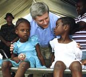 <p>Canada's Prime Minister Stephen Harper talks to two Haitian girls as they wait for treatment at a Canadian medical clinic in Jacmel, Haiti, February 16, 2010. REUTERS/Fred Chartrand/Pool</p>
