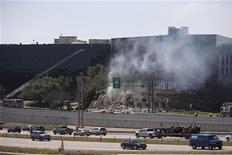 <p>Машины проезжают мимо здания, в который врезался самолет, управляемый Джозефом Эндрю Стэком, Остин, Техас 18 февраля 2010 года. Недовольный налогоплательщик покончил с собой, направив самолет в офис федеральной службы налоговой инспекции. В результате взрыва двое чиновников попали в больницу. REUTERS/Ben Sklar</p>