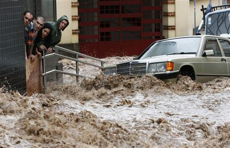 People look on as a street with vehicles is engulfed by heavy flooding in downtown Funchal, Madeira February 20, 2010. REUTERS/Duarte Sa