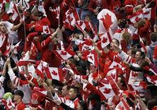 <p>Canada hockey supporters wave flags during the men's preliminary ice hockey game between Canada and Switzerland at the Vancouver 2010 Winter Olympics February 18, 2010. REUTERS/Shaun Best</p>