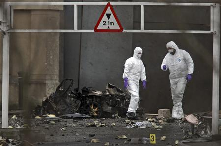 Forensic officers examine the remains of an exploded car bomb outside Newry Courthouse in Newry, Northern Ireland, February 23, 2010. REUTERS/Cathal McNaughton