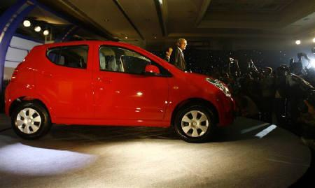 Chairman of Maruti Suzuki India R. C. Bhargava (C) poses with Maruti's new A-Star hatchback model during its launch in New Delhi November 19, 2008. REUTERS/Vijay Mathur/Files