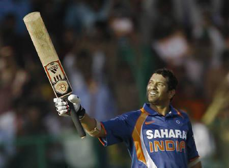 Sachin Tendulkar raises his bat to celebrate his century during the second one-day international cricket match between India and South Africa in Gwalior February 24, 2010. REUTERS/Punit Paranjpe