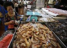 <p>A seafood vendor counts her money at a market in Singapore August 23, 2007. REUTERS/Vivek Prakash</p>