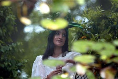 British actress Archie Panjabi, star of films ''East is East'' and '' Bend it Like Beckham'', is reflected in the pond at the Garden of Transparency during the Chelsea Flower Show, London, May 20, 2002. REUTERS/Stephen Hird