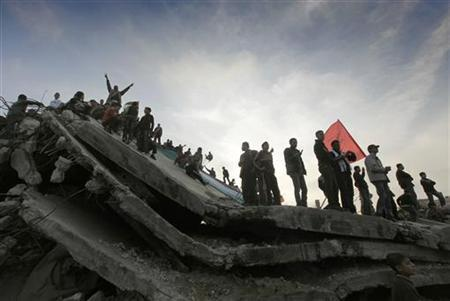 Palestinian supporters of the Popular Front for the Liberation of Palestine (PFLP) stand atop the ruins of a house destroyed during the three-week offensive Israel launched last year, during a rally to mark the first anniversary of the war in Jabalya refugee camp in the northern Gaza Strip on Christmas Day December 25, 2009. REUTERS/Yannis Behrakis