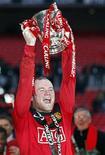 """<p>Форвард """"Манчестер Юнайтед"""" Уэйн Руни держит главную награду Кубка Лиги, 28 февраля 2010 года. Английский """"Манчестер Юнайтед"""" выиграл Кубок Лиги, в финале турнира обыграв """"Астон Виллу"""" со счетом 2-1. REUTERS/Darren Staples</p>"""