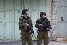 <p>Израильские солдаты патрулируют центр Хеброна 12 февраля 2010 года. Израильские военные отменили спецоперацию в Палестинской автономии после того, как один из солдат опубликовал в социальной сети Facebook время, дату и прочие детали рейда, сообщает израильская военная радиостанция. REUTERS/Ammar Awad</p>