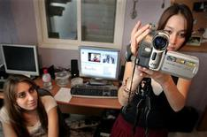 <p>Donne intente a registrare un video da postare su YouTube. Foto d'archivio. REUTERS/Yonathan Weitzman</p>