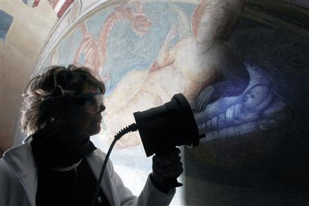 A restorer uses an ultra-violet light to expose greater details on a Giotto painting in the Peruzzi Chapel at the Santa Croce Church in Florence February 26, 2010. REUTERS/Alessandro Bianchi