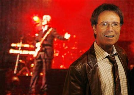 Cliff Richard poses for photographers with his band ''Cliff Richard and The Shadows'' before meeting fans at a music store in London November 30, 2009. REUTERS/Luke MacGregor