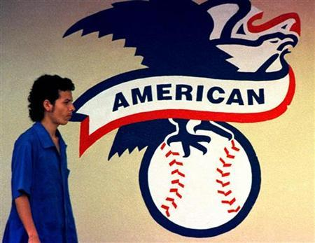 In this file photo an employee of the Rawling baseball factory walks in front of the logo of the American League in Turrialba, 40 miles southeast of the capital San Jose, May 22, 2000. REUTERS/Juan Carlos Ulate