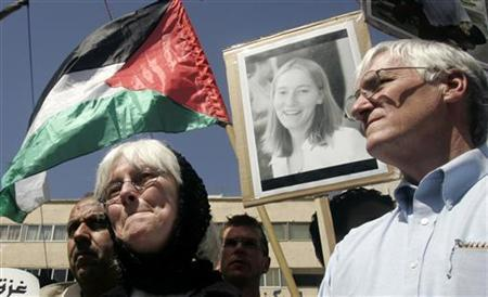 The parents of Rachel Corrie stand in front of her picture during a rally in the West Bank city of Nablus to mark the fifth anniversary of her death March 20, 2008. REUTERS/Abed Omar Qusini