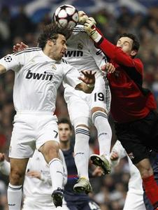 Real Madrid's Raul Gonzalez (L) and Ezequiel Garay try to score past Olympique Lyon's goalkeeper Hugo Lloris during their Champions League last 16, second leg match at Santiago Bernabeu stadium in Madrid March 10, 2010. REUTERS/Juan Medina