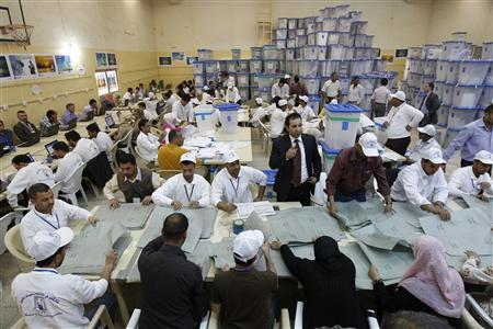 Officials count parliamentary election ballots at the tally centre in Baghdad March 10, 2010. REUTERS/Thaier al-Sudani