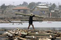 <p>Мужчина тащит бревно в разрушенном землетрясением Пельюуэ, Чили 10 марта 2010 года. Землетрясение силой 6,7 балла по шкале Рихтера произошло в ночь на вторник в Чили, сообщений о жертвах и разрушениях пока не поступало. REUTERS/Victor Ruiz Caballero</p>