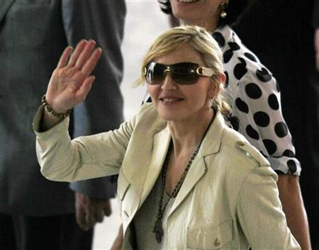 U.S. singer Madonna waves to fans as she arrives at Bandeirantes Palace to meet Sao Paulo's governor Jose Serra February 10, 2010. REUTERS/Paulo Whitaker