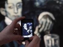 """<p>A man takes a photograph of the """"Portrait of Angel Fernandez de Soto"""" - also known as The Absinthe Drinker by Pablo Picasso, at Christie's auction house in London March 17, 2010. REUTERS/Stefan Wermuth</p>"""