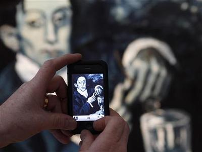 A man takes a photograph of the ''Portrait of Angel Fernandez de Soto'' - also known as The Absinthe Drinker by Pablo Picasso, at Christie's auction house in London March 17, 2010. REUTERS/Stefan Wermuth