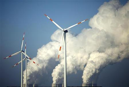 Steam billows from the cooling towers of Vattenfall's Jaenschwalde brown coal power station behind wind turbines near Cottbus, eastern Germany, in this December 2, 2009 file photo. REUTERS/Pawel Kopczynski/Files