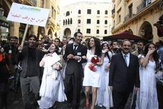 "<p>Lebanese activists walk with Lebanese MP Ghassan Moukhayber (2nd R) in downtown Beirut during a mock civil marriage ceremony March 18, 2010. The placard reads: ""A marriage that is stalled"". REUTERS/ Mohamed Azakir</p>"