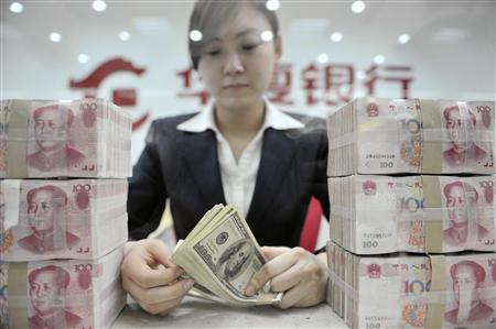 An employee counts U.S. dollar banknotes at a branch of Huaxia Bank in Shenyang, Liaoning province March 18, 2010. REUTERS/Sheng Li