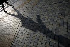 <p>A woman casts a shadow as she walks on a street in Tokyo August 3, 2009. REUTERS/Stringer</p>