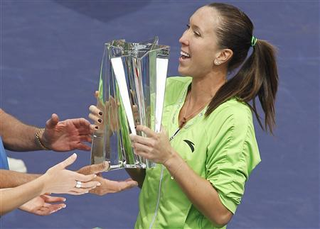 Jelena Jankovic of Serbia gets assistance from others as she attempts to pick up her trophy after defeating Caroline Wozniacki of Denmark in the women's final match to win the Indian Wells WTA tennis tournament in Indian Wells, California, March 21, 2010. REUTERS/Danny Moloshok