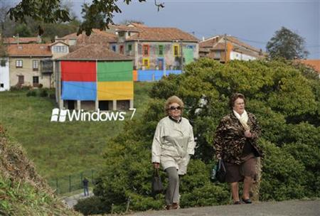 Two women walk in front of the decorated village of Sietes during the presentation of Windows 7, in the northern Spanish region of Asturias, October 22, 2009. REUTERS/Eloy Alonso