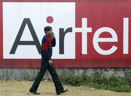 A boy talks on a mobile phone as he walks past a billboard of Bharti Airtel in Amritsar January 18, 2010.REUTERS/Munish Sharma/Files