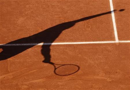 Andy Murray of Britain casts a shadow as he serves during his match against Janko Tipsarevic of Serbia at the French Open tennis tournament at Roland Garros in Paris May 29, 2009. REUTERS/Vincent Kessler
