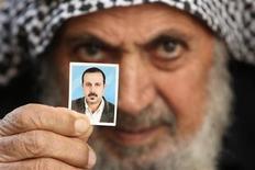 <p>Отец командира ХАМАС Махмуда аль-Мабхуха позирует с фотографией своего убитого сына в Секторе Газа 29 января 2010 года. Великобритания, как ожидается, вышлет во вторник израильского дипломата за использование поддельного британского паспорта подозреваемыми в убийстве одного из командиров ХАМАС в Дубае. REUTERS/Mohammed Salem</p>