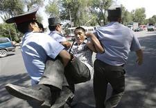 <p>Сотрудники милиции несут задержанного сторонника оппозиции в центре Бишкека 29 июля 2009 года. Киргизская милиция во вторник в ходе столкновений с митингующими задержала несколько десятков сторонников оппозиции, протестовавших против ужесточения политики властей. REUTERS/Vladimir Pirogov</p>
