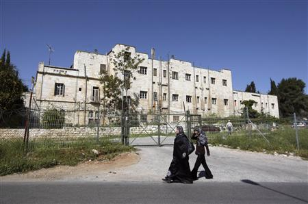 Women walk in front of the compound known as the Shepherd's Hotel in the Sheikh Jarrah neighbourhood of East Jerusalem, March 24, 2010. REUTERS/Ammar Awad