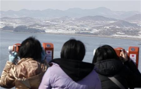 Visitors look at a village in North Korea's Kaepoong county through binoculars in this picture taken from a South Korean observation post near the demilitarised zone (DMZ) separating the two Koreas in Paju, about 50 km (31 miles) north of Seoul, February 16, 2010. REUTERS/Jo Yong-Hak
