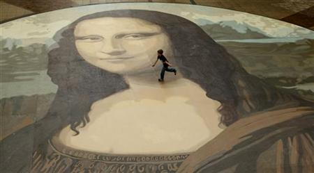 A boy runs across a giant copy of the Mona Lisa as it is unveiled in Wrexham, north Wales, October 28, 2009. REUTERS/Phil Noble