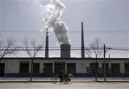A man selling brooms rides his bicycle past abandoned buildings in front of a chimney billowing smoke from a nearby coal-burning power station in Beijing March 10, 2010. REUTERS/David Gray