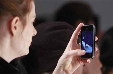 A woman takes a picture with her iphone during the Dennis Basso Fall 2010 fashion show during New York Fashion Week, February 16, 2010. REUTERS/Brendan McDermid