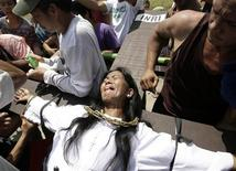 <p>A penitent bites her tongue as she is nailed to a wooden cross as part of a voluntary ritual to mark the death of Jesus Christ on Good Friday in the town of San Juan in Pampanga province, north of Manila April 2, 2010. REUTERS/Cheryl Ravelo</p>