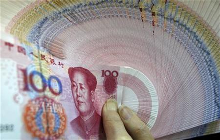 An employee poses with China yuan notes at the Bank of Taiwan head office in Taipei, March 8, 2010. REUTERS/Nicky Loh